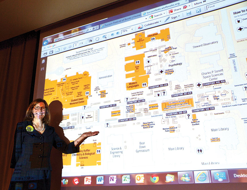 Executive Director of the Tucson Festival of Books, Marcy Euler, shows TWOQC the website map of planned events at the festival.