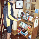 Frank Cobarrubias looking for books on the clubhouse Library's new book cart