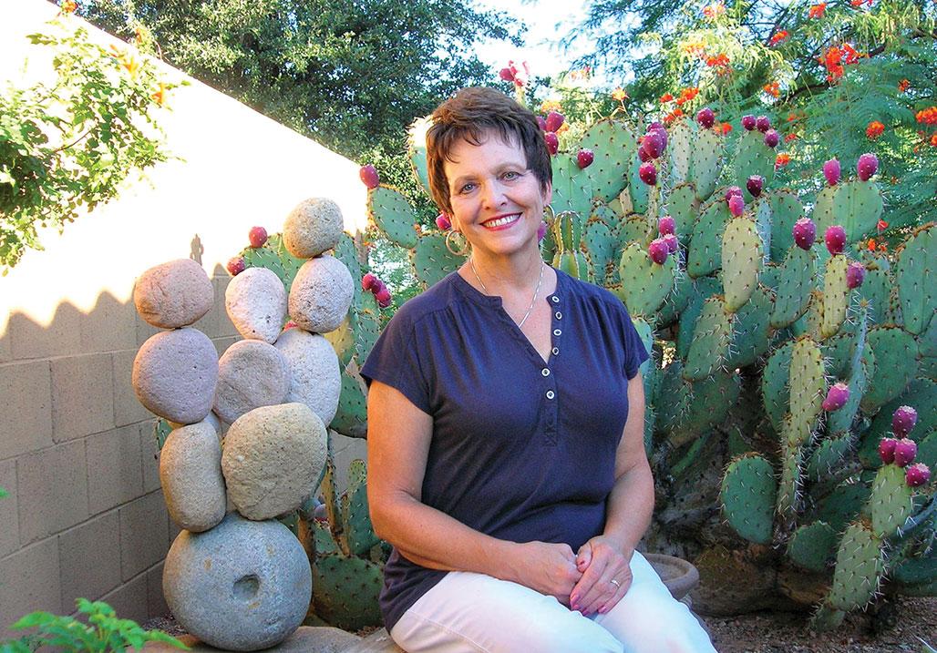 Kathy Stone sits amongst her cacti; photo by Ron Sullivan.