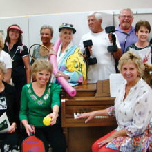 Cyndy Gierada and Jeri Collins, seated at the piano, work with the singers as they present life at Quail Creek. How many activities can you identify?