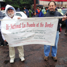 """From left: Father Peter Neeley, J.S., KBI Assistant Director of Education and Shel Zantkin holding the banner in front of the Comedor that translates from Spanish: """"In the Church, no one is a foreigner,"""" John Paul II"""