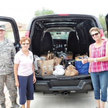 Left to right: Captain (Chaplain) Nathan Mestler, 162nd Wing, Arizona Air National Guard, TWOQC President Peggy McGee and 162nd Family Readiness Program Manager Barbara Gavre with just some of the food and household items that Quail Creek residents donated to show their support for the Airmen and their families; photo by Steve Abel.
