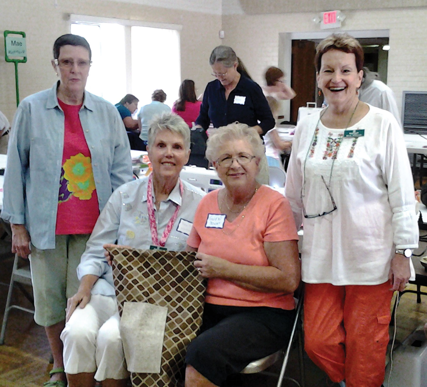 Mary Cerny, Barb Poltl, Gwen Mowat and Max Perzan display a cloth bag.