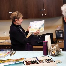 Resident Jean Pastore demonstrates watercolor painting with students attending her recent class. Jean will teach basic watercolor technique again in a Come and Try It workshop on January 14.