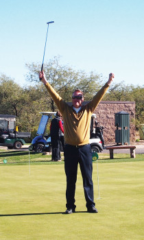 Golf Pro Joel Jaress raised his putter in victory when he got a hole-in-one on his 18th try; photo by Sylvia Butler