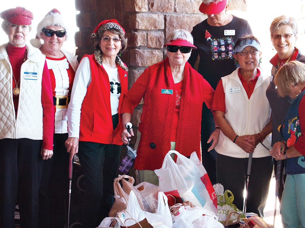 Lady Putters stand behind one of the totes that were filled with groceries destined for the Food Bank; photo by Sylvia Butler.