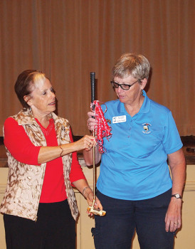 Left to right: Outgoing President Dee Waggoner presents the golden putters to newly elected President Cathy Thiele; photo by Sylvia Butler