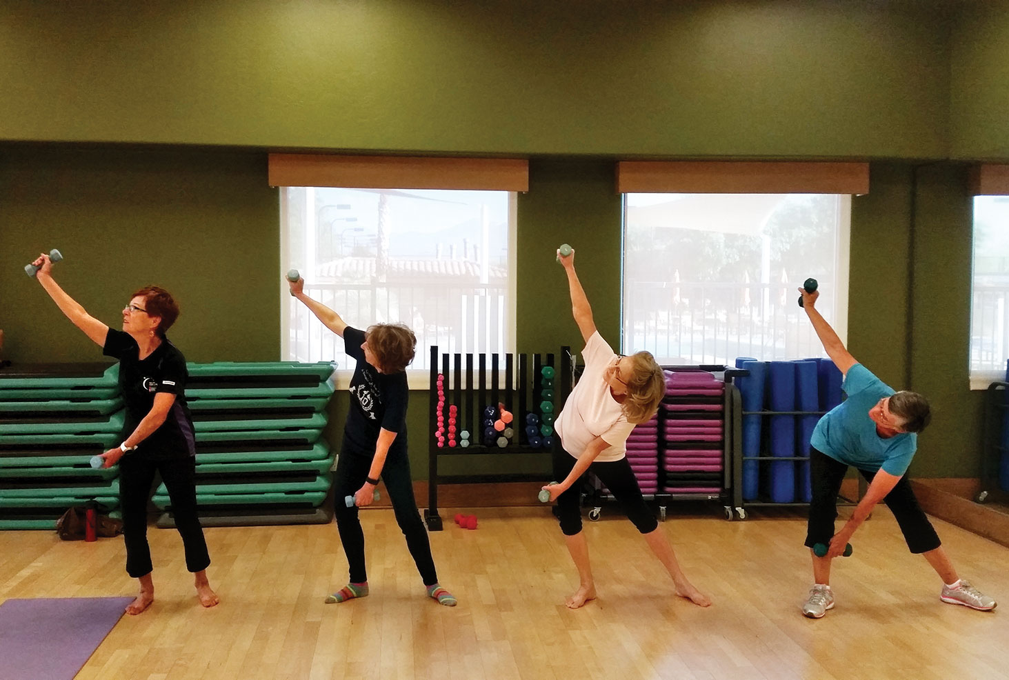 Left to right: Peggy McGee, Joanne Stockbower, Mary Hassler and Ruth Rossi go through some controlled stretches using weights; photo by Aprylmarie Heule