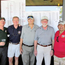 Gunter Schmidt, Tom Haberer, Brian Kuehn, Dave Burrows and tournament Chairman Rene Gill gather at the leader board following the tournament.