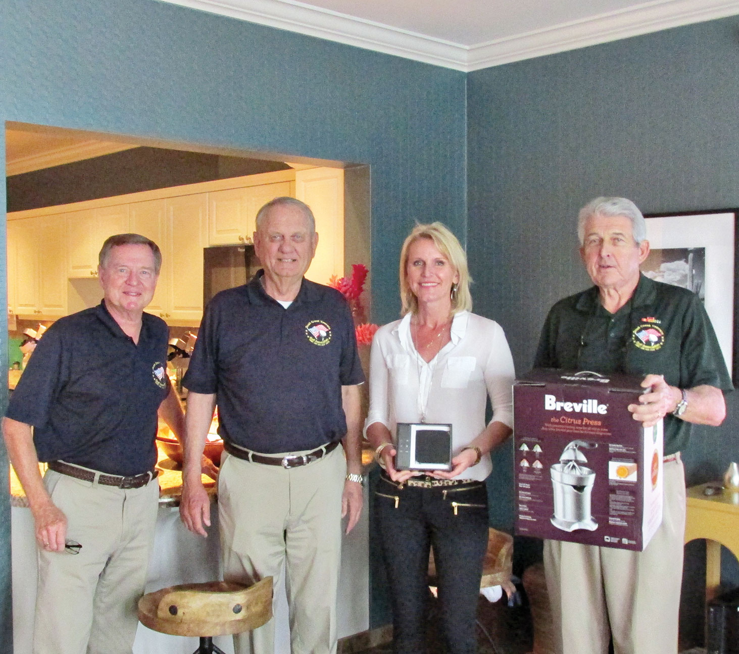 QCVGA Board members Tom Haberer, Ted Schelenski and David Ray present needed items to Kelly Laurich, director of Tucson's Fisher House.