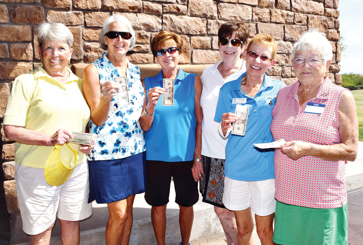Left to right: Susan Kuehn, Chris Gould, Judy Murray, Gail Phillips, Sherry Ameling and Barb Haley proudly wave their $5 bills for scoring five Holes-In-One; photo by Eileen Sykora