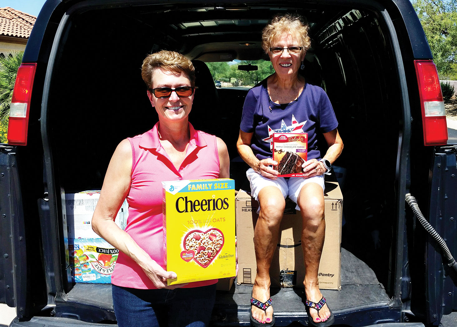 Left to right: Barbara Gavre and Peggy McGee show off just some of the grocery items that were donated during the Food for the Troops drive; photo by John McGee