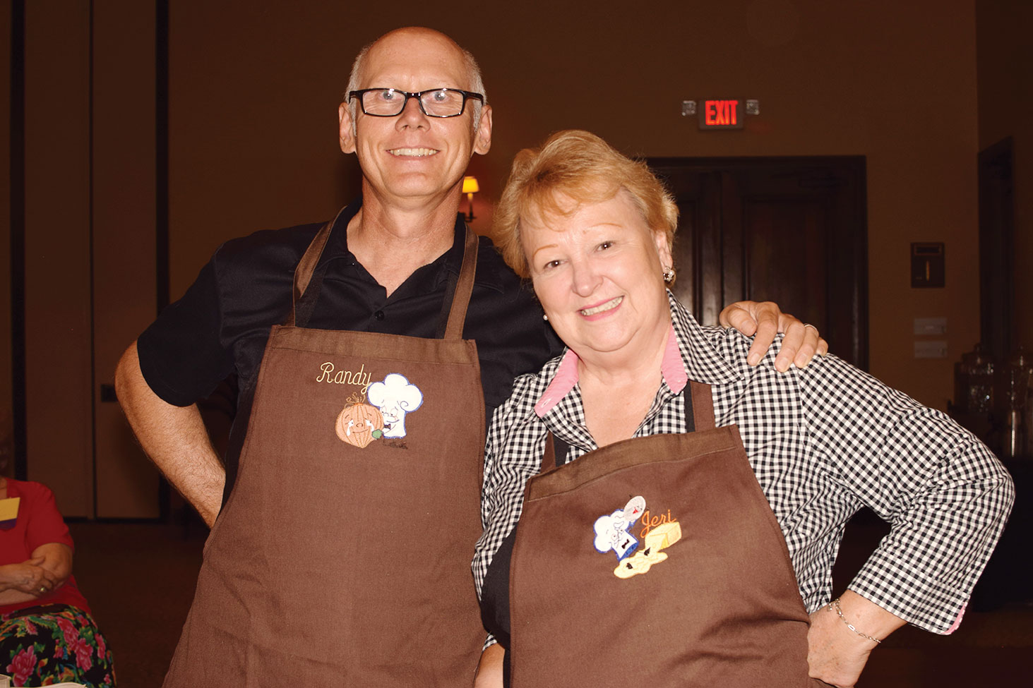 Randy and Jeri were happy to receive aprons made for them by TWOQC member Sue Ann Obremski; photo by Eileen Sykora