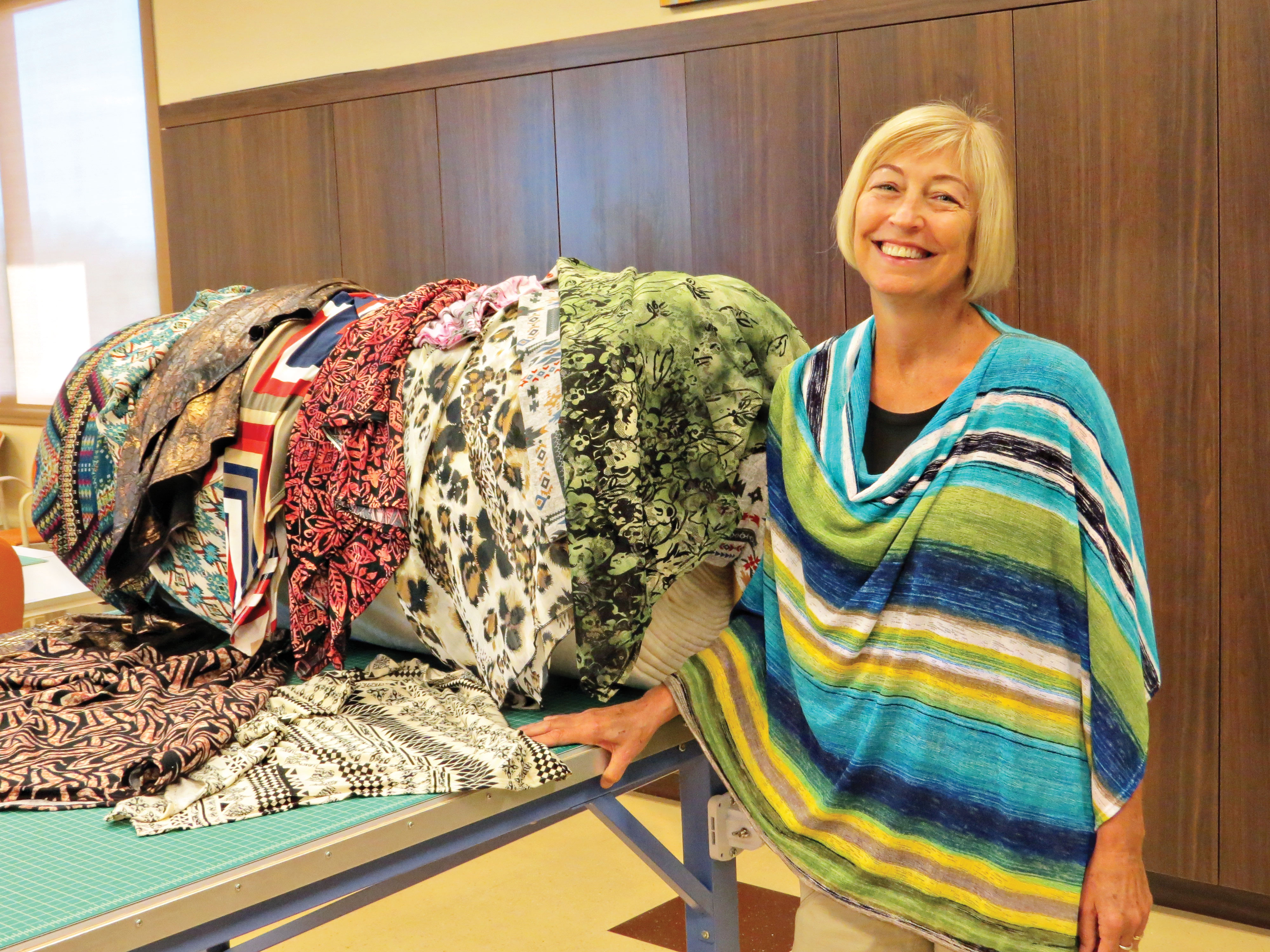 Debbie Huber has fun modeling one of the Perfect Wraps next to fabric of some of the other choices; photo by Diane Quinn.