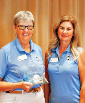 Cathy Thiele is all smiles as Kelly Hines, Putters vice president, presented her with the crystal golf ball for having 12 holes-in-one; photo by Sylvia Butler