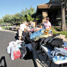 TWOQC volunteers sorting men's and women's clothing donations; photo by Diane Quinn