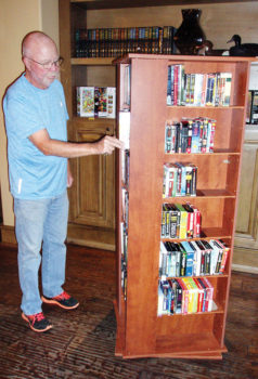 Longtime donations coordinator Phil Geddes at the audio book-DVD movie carousel