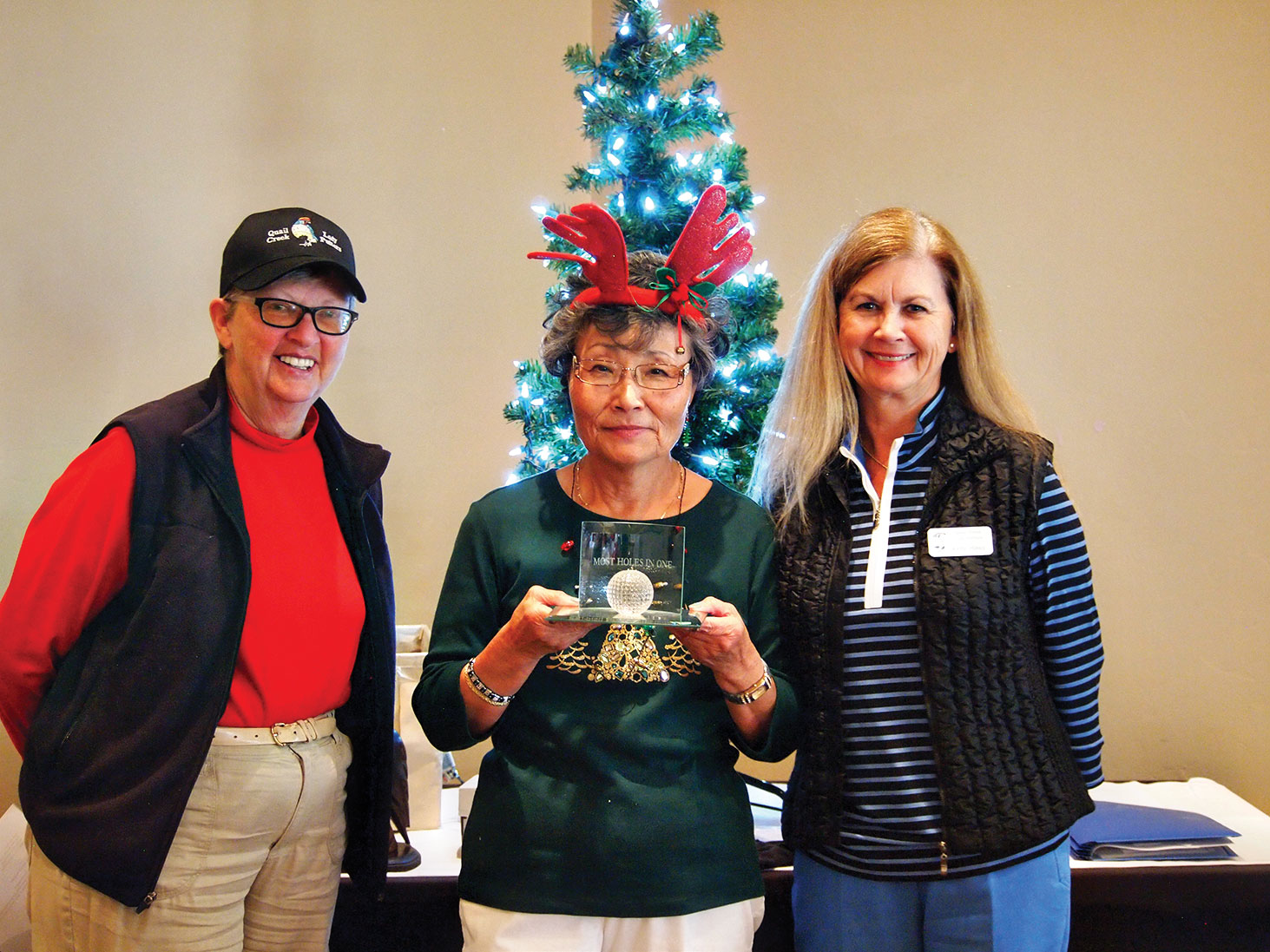 Left to right: Cathy Thiele, Yoshie Hennessy and Kelly Hines all admired Yoshie's award for getting 26 holes-in-one during a three month period; photo by Sylvia Butler