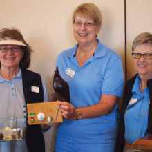 Jan Ederle holds the Crystal hole-in-one plaque and award plaque for the lowest gross score while Club Vice President Janet Wegner holds the Coveted Quail for low net score, with President Cathy Thiele looking on; photo by Sylvia Butler.