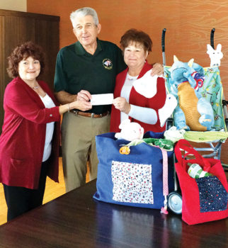 Daniel Ray of the Quail Creek Veterans' Golf Association presents a check to baby shower co-chairs Kathi Krieg (left) and Pam Rodgers.