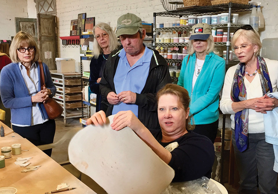 Donna Stoner demonstrates how to make clay the correct leather-like consistency and thickness for cutting shapes. The shapes, when finished, will become part of one of Santa Teresa's colorful mosaics.