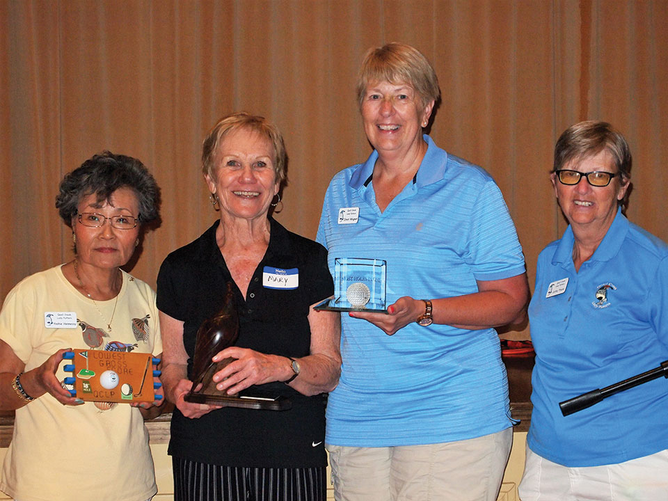 Left to right: Yoshie Hennessy, Mary Fowler and Janet Wegner hold their trophies while Putters President Cathy Thiele looks on; photo by Sylvia Butler.