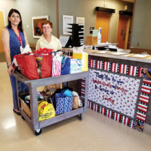 Jodi Frederick, Homeless Program Coordinator at the VA Hospital, looks over the gift bags delivered by Peggy McGee; photo by Eric Jacobson.