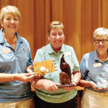 Left to right: Janet Wegner holds the Low Score plaque while Wendy Van Dyck holds the Coveted Quail. Cathy Thiele shows off the crystal golf ball for the most holes-in-one; photo by Sylvia Butler