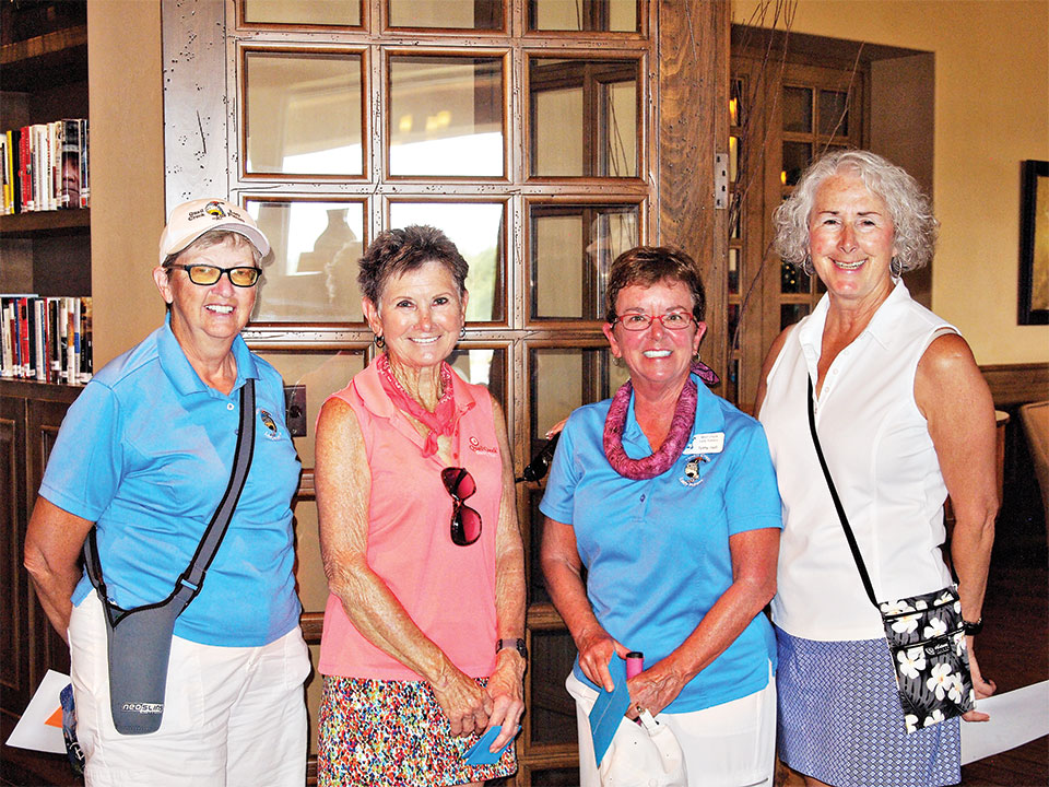 Left to right: Cathy Thiele with the individual low score winners, Christine England and Patty Hall with Chris Gould looking on; photo by Sylvia Butler
