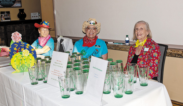 From left: Margaret Morris, Suzanne Whisler, and Joanna Miller selling commemorative beer pint glasses with the Javelina Hoedown logo.