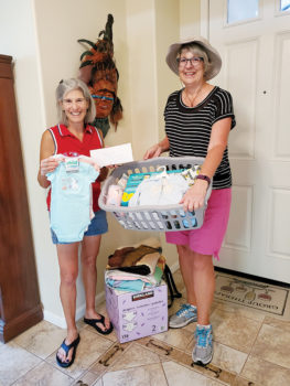 Karen Baker (left), chair of TWOQC's baby shower committee, is presented with a check for $320, along with a laundry basket full of baby items and diapers courtesy of the Lady Putters from Janet Wegner (right). (Photo by Monte Hudson)