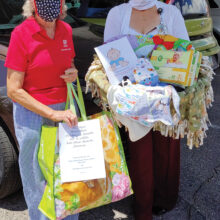 (Left to right) Peggy McGee and Karen Kuciver hold the layette items for the new baby and his mom. (Photo by Pat Crutcher)