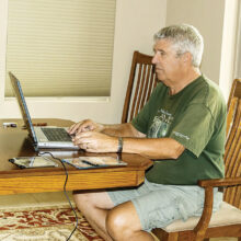 """Jim Burkstrand performs """"brain surgery"""" on one of the donated laptops. (Photo by Marilyn Burkstrand)"""