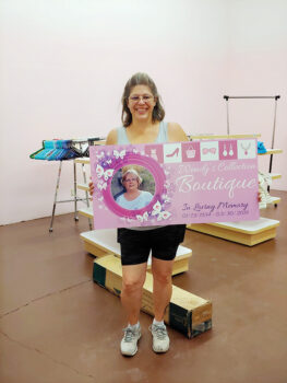 Karen Kuciver holds the Wendy's Boutique sign as she begins work on organizing the thrift shop. (Photo by Peggy McGee)