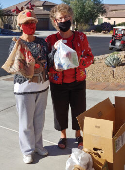 Kathy Guy (left) hands some food donations to Sharon Schoen. (Photo by Peggy McGee)