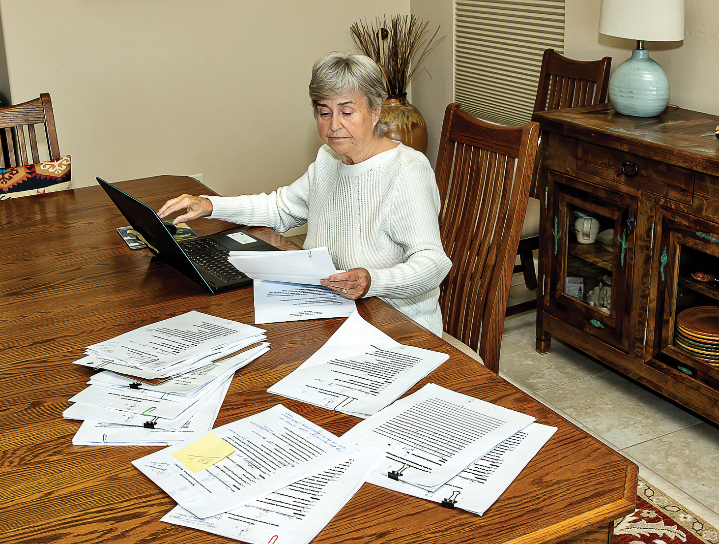 Screening team member Marilyn Burkstrand reviews applications, both online and in hard copy, to make her recommendation for which women should be scheduled for an interview. (Photo by Jim Burkstrand)