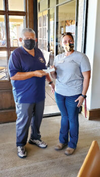 Rene Gill, QCVGA president, presents a check to TROT development director, Margaux DeConcini.