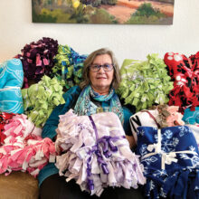 Laura Colbert is surrounded by some of the blankets she made for Women Warriors at Christmas time. (Photo by Jerry Colbert)